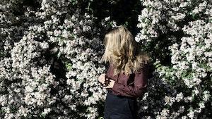 Nina Nielsen i blomsterhage med hår som blåser