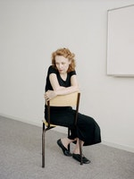 Kaija Saariaho sitter på en stol i et hvitt rom