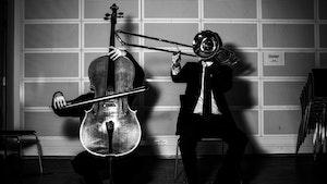 Cellist og trombonist med instrumentene foran ansiktene