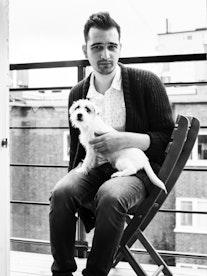 Koka Nikoladze sitter med en hund på fanget