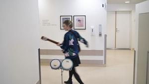 Musikkterapeut Monika Overå bærer på trommer og gitar inne på sykehus