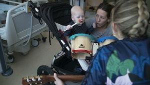 Musikkterapeut Monika Overå spiller gitar for baby og mamma på sykehus