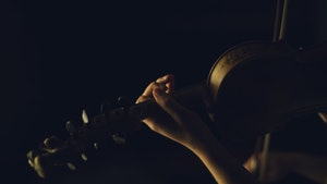 Hender som spiller hardingfele i mørket