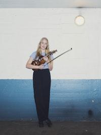 Helga Myhr står foran blå og hvit vegg med fela