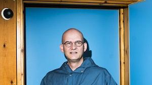Peter van Tour står foran en knallturkis vegg