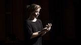 Tabita Berglund står i mørket og ser på hendene sine