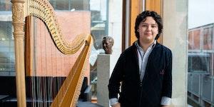 Emmanuel Padilla Holguín står ved siden av harpen sin i Prismerommet
