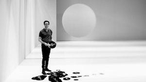 Svart-hvittbilde av Erik Dæhlin som står i et stort hvitt rom og holder vinyler