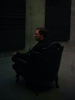 Erik Dæhlin sitter i en sto lenestol i et mørkt rom