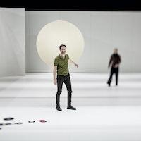 Erik Dæhlin står i et stort hvitt rom med vinyler på gulvet