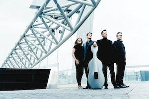 En dame og tre menn står på en bro i Bjørvika i Oslo og ser mot horisonten. En av dem lener seg mot en cello.