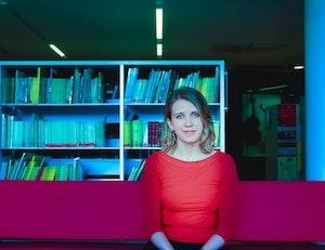 Aliisa Neige Barriere sitter foran en hylle i biblioteket på NMH.