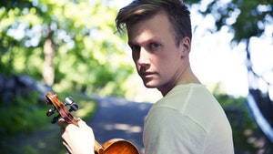 Bjørn Kåre Odde med fiolin foran skogsvei
