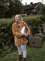 Cathrine Winnes står i hagen sin med partitur og dirigentpinne