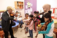 Barn med hver sin fiolin står vent mot en underviser.