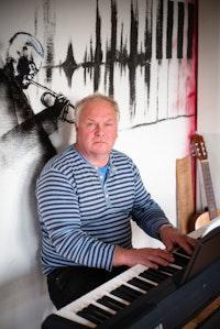 Homeside-deltaker Harald spiller piano foran vegg med trompetspiller-veggmaleri