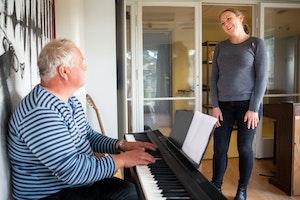 Homeside-deltaker Harald spiller piano mens Kristi Stedje ser på