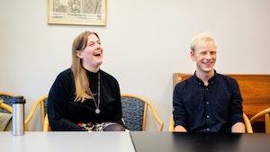 Hugo Gjelsvik Herrman og Guro Utne Salvesen sitter ved et bord og ler