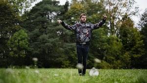 Jens Linell står i en eng med armene opp. Tamburinen hans ligger ved siden av.