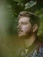 Nærbilde av profilen til Jens Linell mellom grener