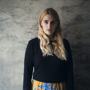 Larissa Terescenko står foran grå vegg og ser inn i kameraet
