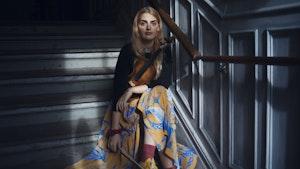 Larissa Terescenko sitter i trapp med fiolinen på fanget