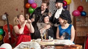 Gruppebilde av Majorstuen (band) som sitter ved et bord i finstasen og skåler