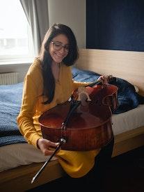 Cellist María Alejandra Conde Campos sitter på seng og skrur på celloen sin