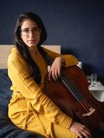 Cellist María Alejandra Conde Campos sitter på sengen med celloen