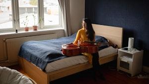 Cellist María Alejandra Conde Campos sitter på sengen med celloen på fange og ser vekk