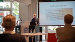 Fra seminaret om NMHs historieprosjekt. Einar Solbu på talerstolen foran en skjerm som viser utdrag av privatskoleloven.