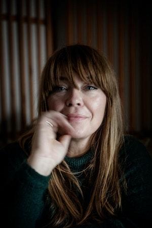 Solveig ser mot kameraet og fører en hånd mot ansiktet. Hun har tung pannelugg og smiler lett.
