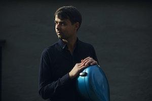 Theodor Lyngstad  står i et mørk rom med en cello og ser til venstre.