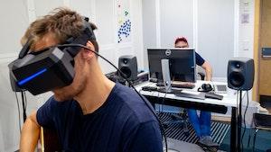 Johannes Lunde Hatfield sitter og spiller gitar med VR-briller på. Pål Hieronimus Aamodt sitter i bakgrunnen bak PC'en