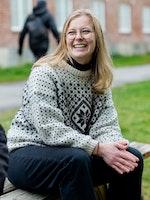Andrine Erdal sitter på et parkbord og smiler