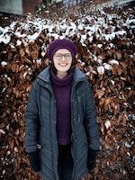 Astrid Kvalbein i helfigur foran en snødekt hekk med oransje vinterblader. Astrid har lilla alpelue og mørk grå boblejakke og smiler mot kamera.