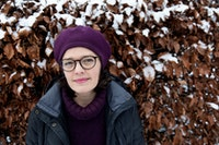 Astrid in front of snow-covered hedge smiling towards the camera. She is wearing a beret, round spectacles and a winter jacket.