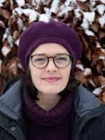 Portrett av Astrid Kvalbein med lilla alpelue foran en oransje hekk med snø på.