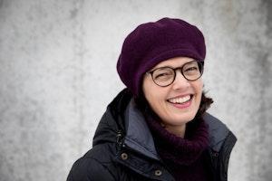 Astrid står mot en murvegg, ikledd lue og boblejakke, og smiler bredt mot kameraet.