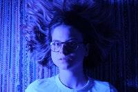 Blåaktig bilde av Astrid Solberg som ligger på et teppe med håret ut
