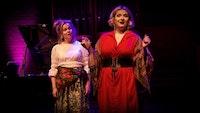På bildet er det to kvinnelige studenter i kostymer som er midt i en operascene