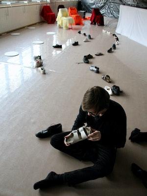 NMH-student sitter på gulvet med masse sko på en rekke bak seg. Han har en sko i fanget som han ser på.