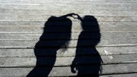 Skyggen av to personer som lager et hjerte med hendene, foran en vegg.