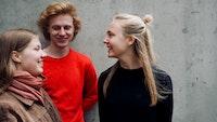Kongle Trio står og smiler til hverandre foran betongvei