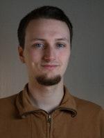 Portrett av Mikkel Alvheim Åse, med brun skjorte foran grå vegg.