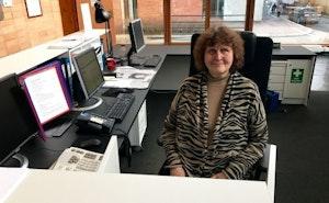 Vera Scott Stenersen sitter i resepsjonen på NMH og smiler.