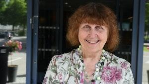 Vera Scott Stenersen står foran inngangen til NMH og smiler.