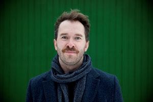 Eyolf Dale foran en grønn vegg. Smiler mot kamera.