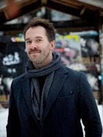 Eyolf Dale står smilende i mørk jakke og skjerf foran en butikk med skråtak