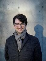 Julius Pranevicius smilende med frakk og skjerf foran en betongvegg